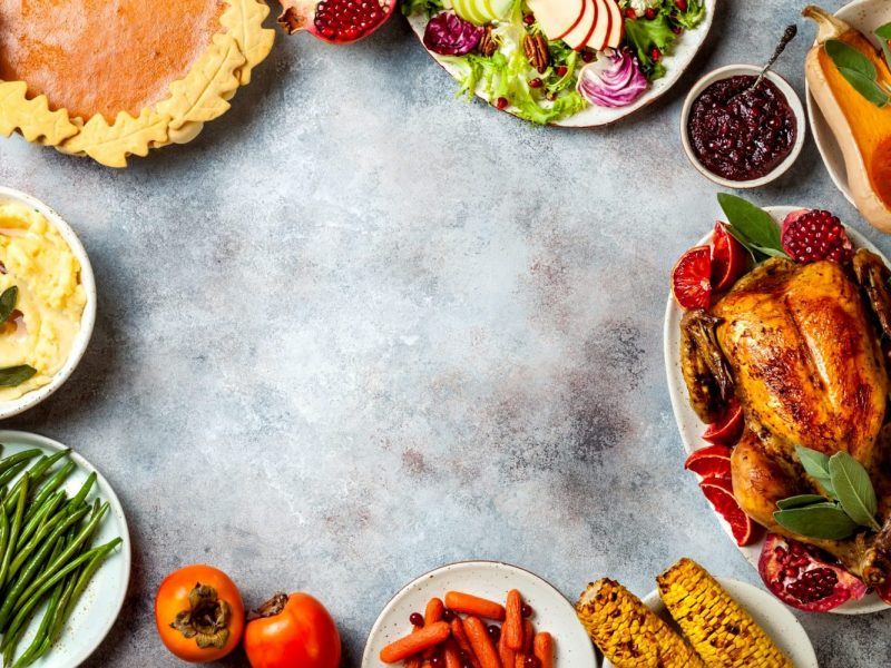 Thanksgiving dinner table with roasted whole chicken or turkey, green beans, mashed potatoes, cranberry sauce and grilled autumn vegetables. Top view, frame.