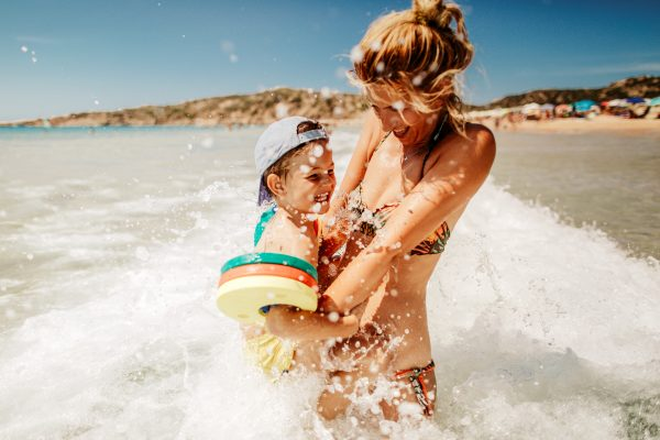 Photo is showing young mother with her son, enjoying bathing in a sea water