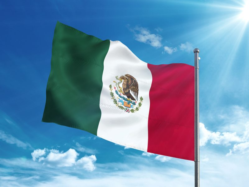 Mexican flag waving in the blue sky